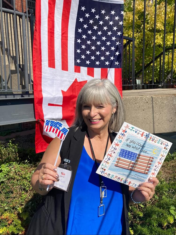 Author Tina Powell stands in front a draped flag, which shows both American and Canadian icons (starts, maple leaf). She is holding her book in one hand an a flag in the other.