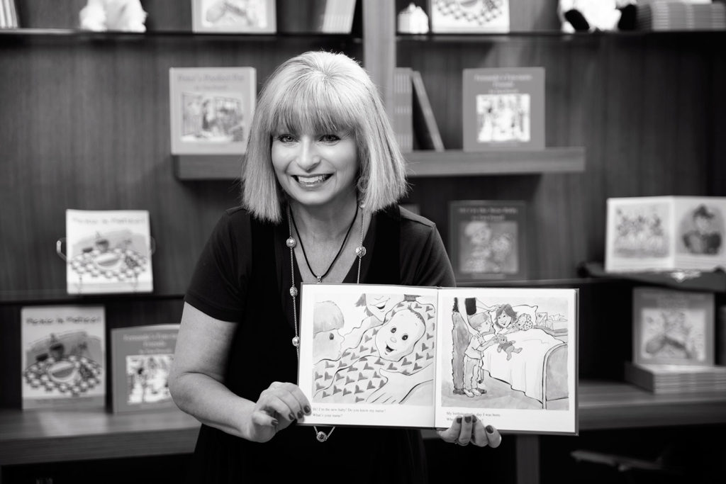 Black and White photo of author Tina Powell holding her children's book open to a page with an illustration of a baby on the left and a boy looking at him, and on the right the same boy holding a teddy bear. His mom and baby are in bed.