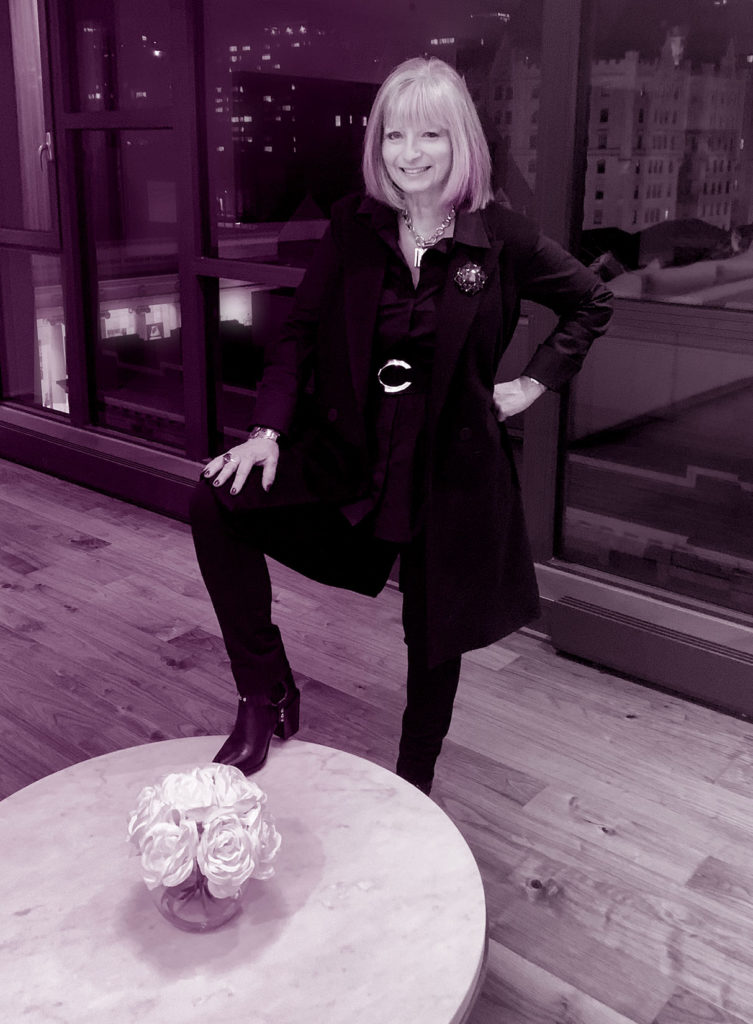 Tina Powell poses with one leg up on a table. A vase of flowers on table. In the background is a city view. The image is a  tritone, black and white treated with purple hues.